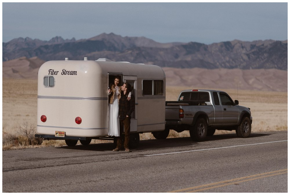 Olivia and Justin's couple photos near their refurbished Fiber Stream trailer that they road tripped across the US in for their Southern Colorado winter elopement. Photo by Maddie Mae Photo, Adventures Instead.