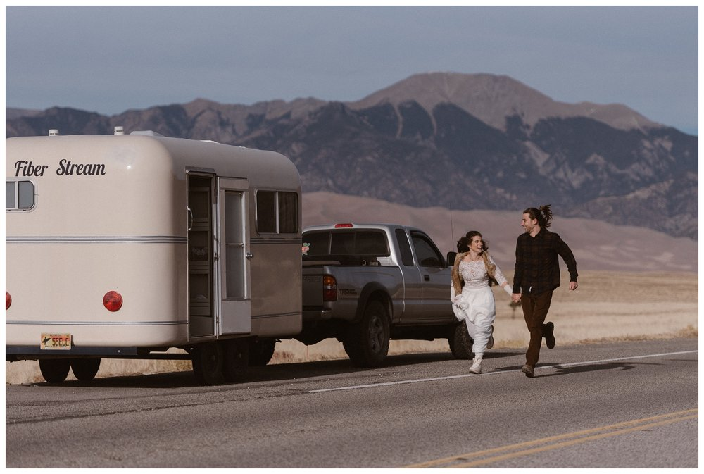 Olivia and Justin run alongside their renovated Fiber Stream camping trailer before their winter elopement at Great Sand Dunes National Park. Photo by Maddie Mae Photo, Adventures Instead.