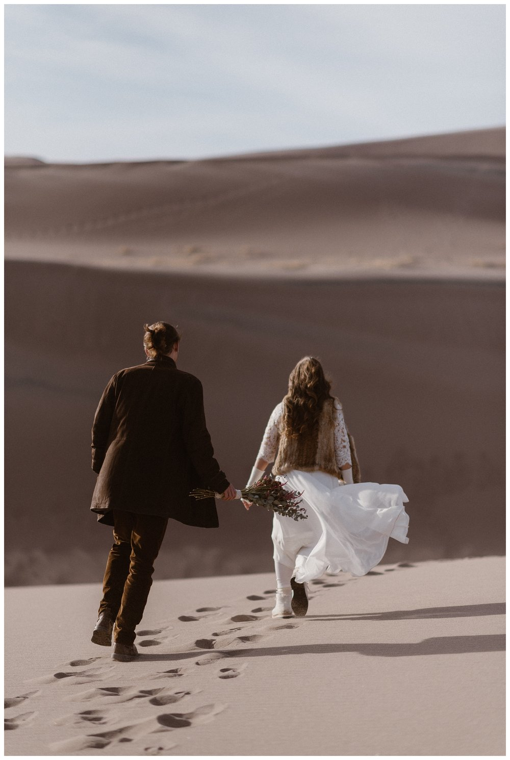 The wind blows Olivia's white bridal skirt as she walks along Great Sand Dunes National Park during a winter adventure elopement. Photo by Maddie Mae Photo, Adventures Instead.