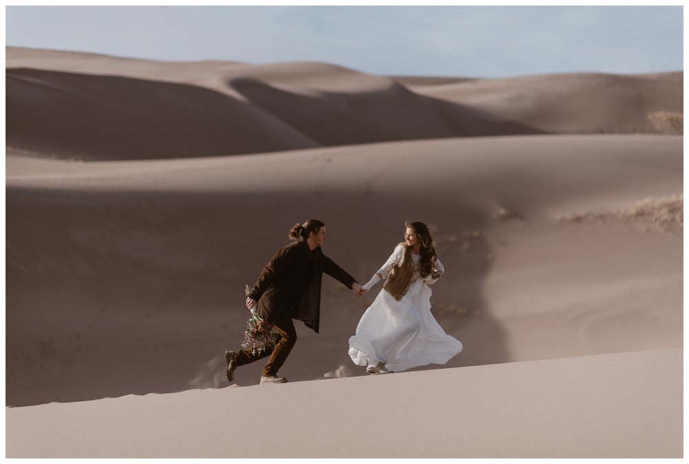 Running along the dunes before their winter Colorado Elopement. Photo by Maddie Mae Photo, Adventures Instead.