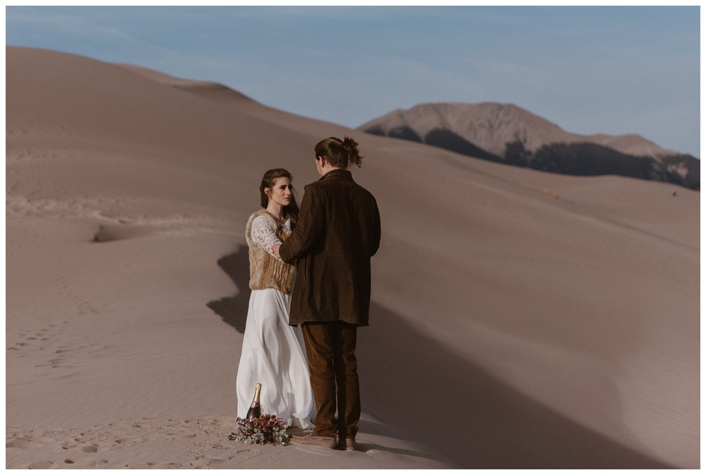 Olivia and Justin stand on the dunes during their private, intimate wedding elopement ceremony at Great Sand Dunes National Park. Photo by Maddie Mae Photo, Adventures Instead.