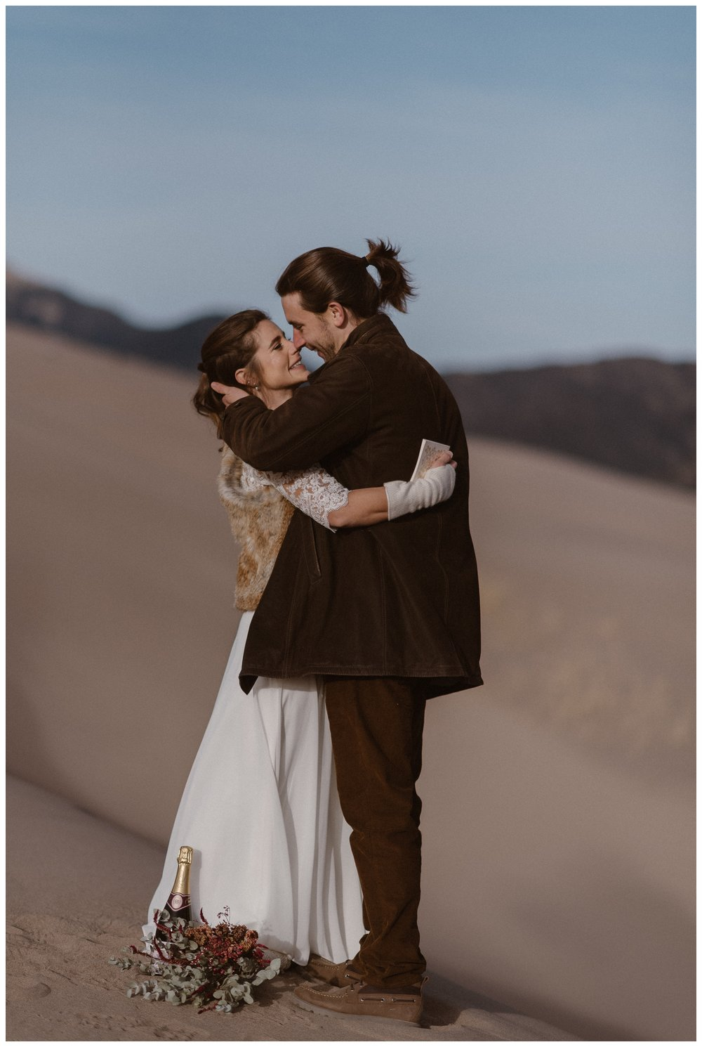 Newly married, Olivia and Justin embrace after their intimate elopement on top of the dunes in Southern Colorado. Photo by Maddie Mae Photo, Adventures Instead.