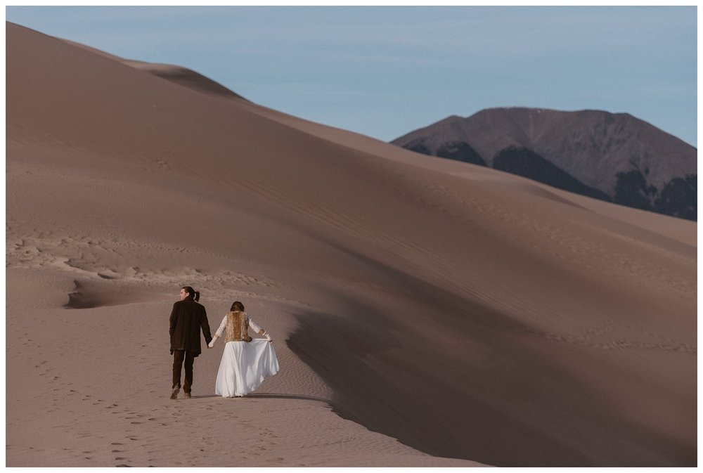 Bride and groom enjoy a long walk alone after their intimate self solemnizing ceremony on top of Great Sand Dunes National Park. Photo by Maddie Mae Photo, Adventures Instead.
