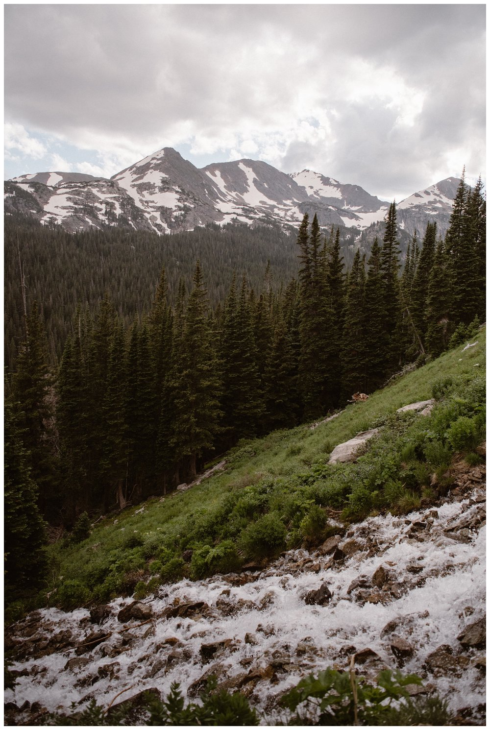 Spring snow runoff flows down the side of the Rocky Mountains during a hiking elopement. Photo by Maddie Mae Photo, Adventure Instead.
