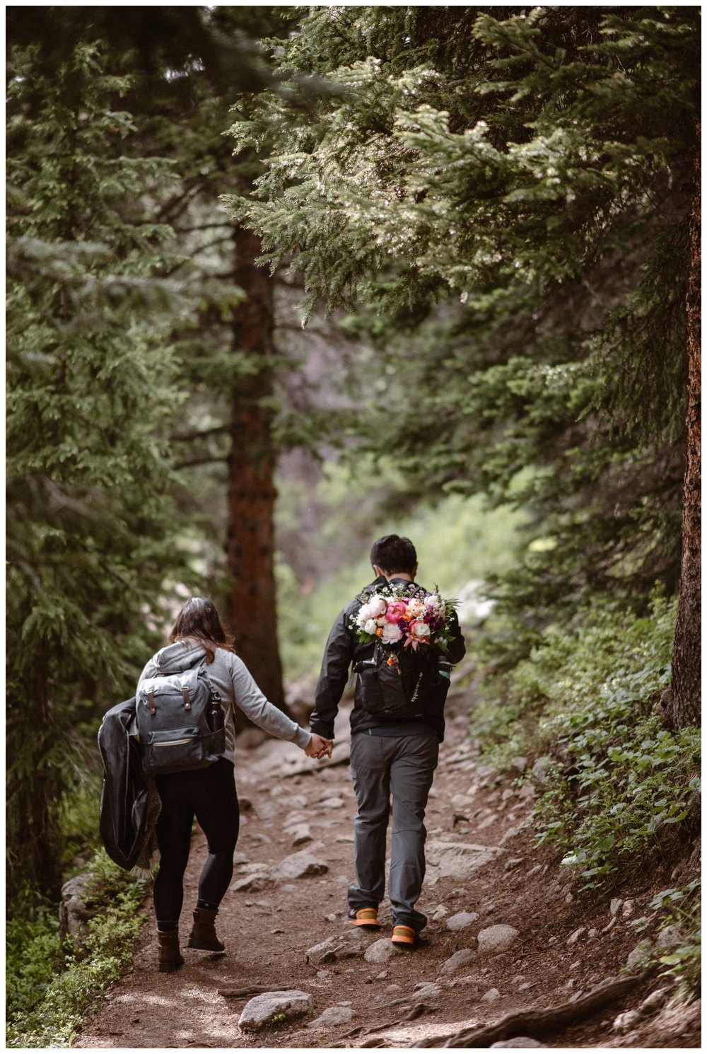 As they climb the trail towards Gem Lake for their hiking elopement, Leslie and Jinson carry their wedding attire and her bouquet on their backs. Photo by Maddie Mae Photo, Adventure Instead.
