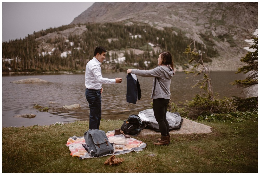Leslie and Jinson help each other get dressed and ready for their high alpine lake elopement ceremony at the shores of Gem Lake. Photo by Maddie Mae Photo, Adventure Instead.