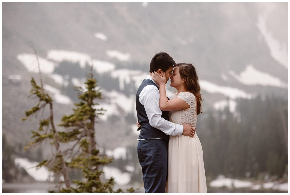 Spring snow is still visible behind Leslie and Jinson as they embrace after their high alpine lake elopement at Gem Lake in Estes Park Colorado. Photo by Maddie Mae Photo, Adventure Instead.