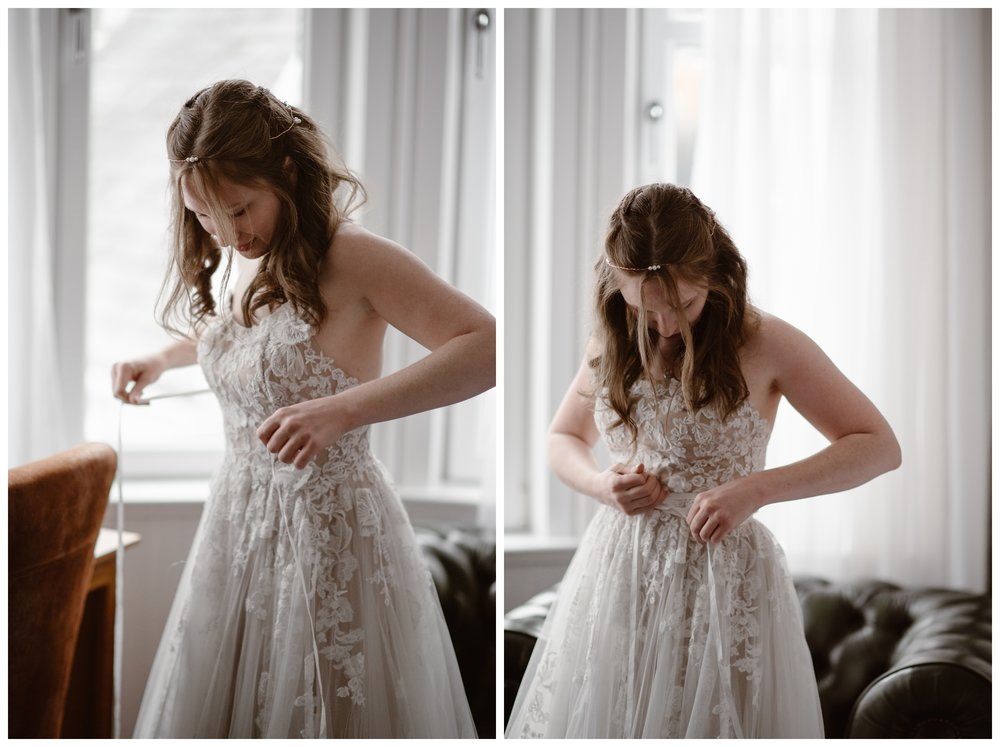 Elissa ties her flowing lace wedding dress she had brought overseas for her Scotland elopement outside Kilchurn Castle and Glencoe in the Scottish Highlands. Photo by Maddie Mae, Adventure Instead.
