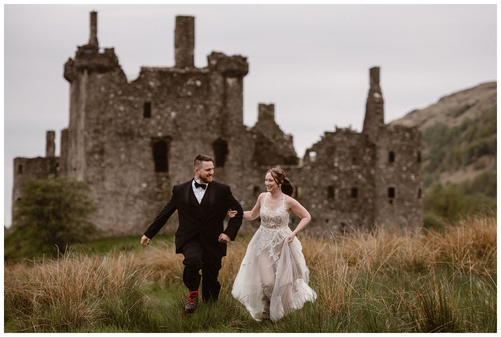 Elissa and Daniel run through the Scottish Highlands with Kilchurn Castle behind them before their destination wedding elopement. Photo by Maddie Mae, Adventure Instead.