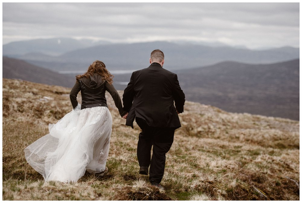 Elissa and Daniel hike through the Scottish Highlands in their wedding day clothing as they search for the perfect unique spot to say their vows outside Glencoe, Scotland. Photo by Maddie Mae, Adventure Instead.