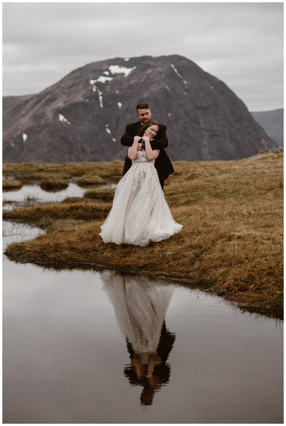 Elissa and Daniel embrace and are reflected in the water a loch in the Scottish Highlands during their destination elopement. Photo by Maddie Mae, Adventure Instead.