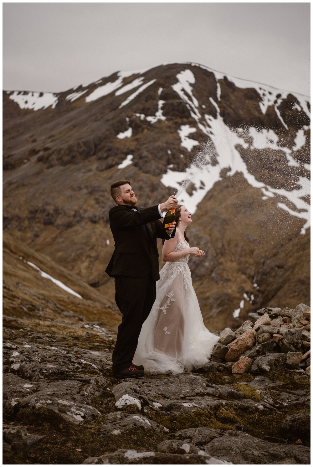 Elissa and Daniel celebrate saying their vows in the Scottish Highlands outside Glencoe, Scotland, with a bottle of champagne. Photo by Maddie Mae, Adventure Instead.