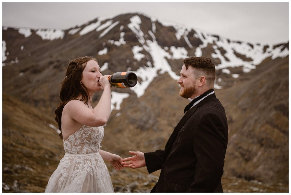 Elissa drinks champagne directly from the bottle following her Glencoe Scotland elopement ceremony. Photo by Maddie Mae, Adventure Instead.