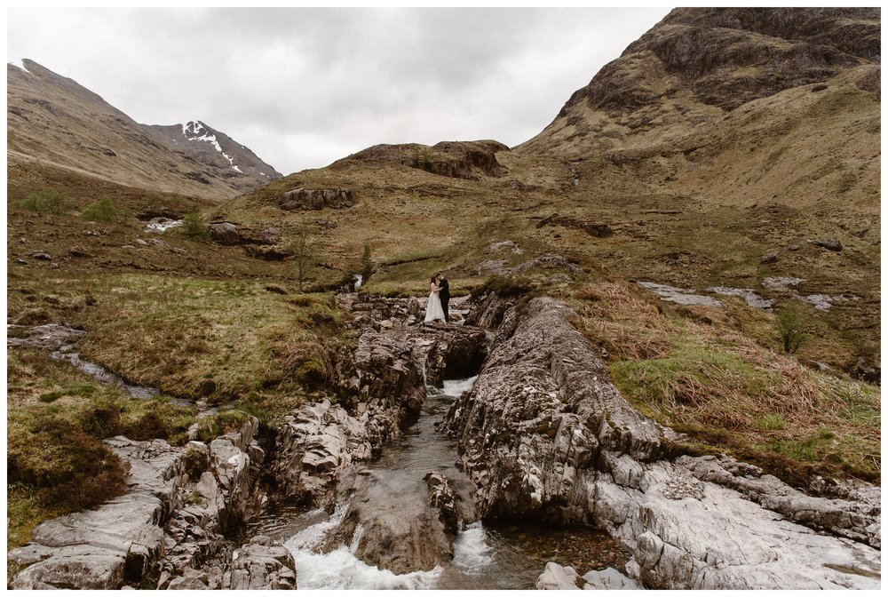 Water flows through the Scottish Highlands as Elissa and Daniel are dwarfed by the rocky marsh landscape following their destination elopement ceremony. Photo by Maddie Mae, Adventure Instead.
