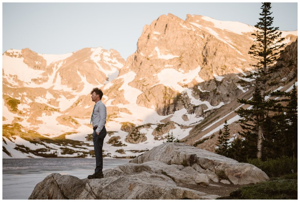 Matt waits for his first look of his bride as the alpenglow makes the mountains behind Lake Isabelle glow pink before their adventure elopement ceremony. Photo by Adventure Instead, Maddie Mae.