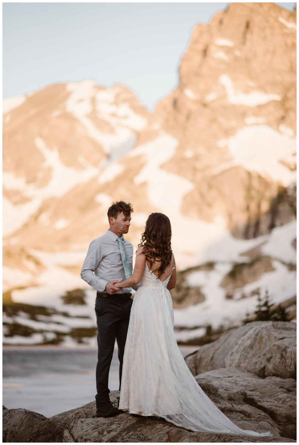 The mountains behind Lake Isabelle glow pink in the early morning dawn hour before Karen and Matt's adventure hiking elopement ceremony. Photo by Adventure Instead, Maddie Mae.