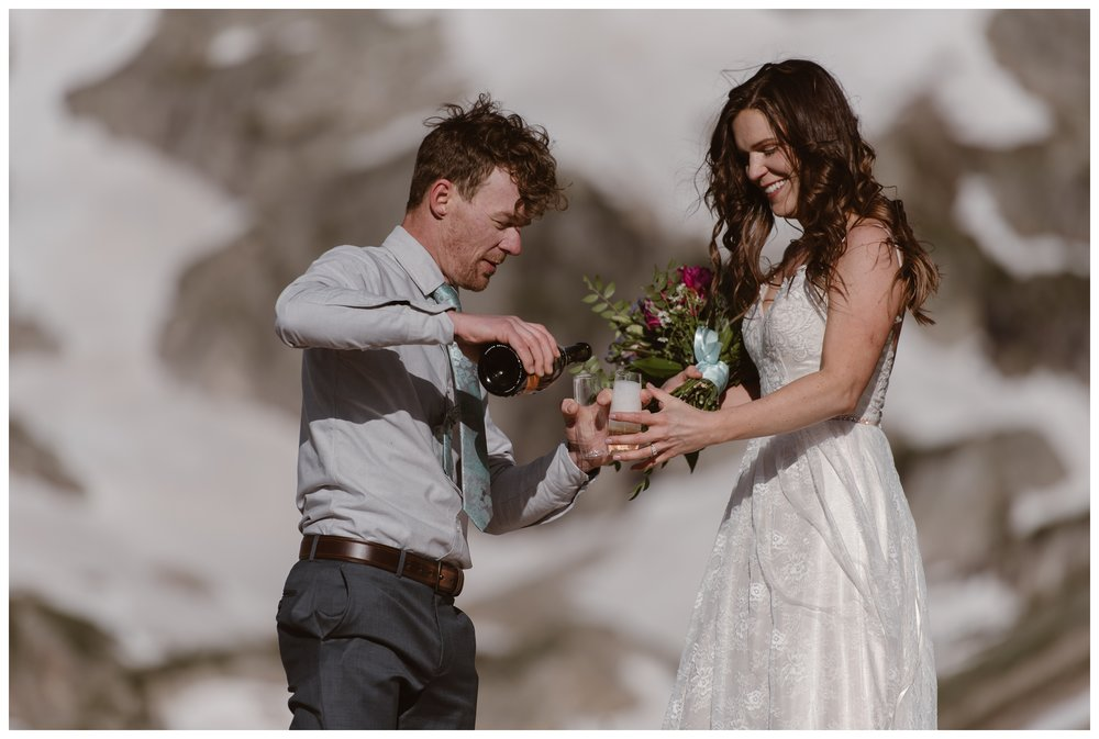 Matt and Karen share a glass of champagne to celebrate after their self solemnizing hiking elopement ceremony in Nederland, Colorado. Photo by Adventure Instead, Maddie Mae.