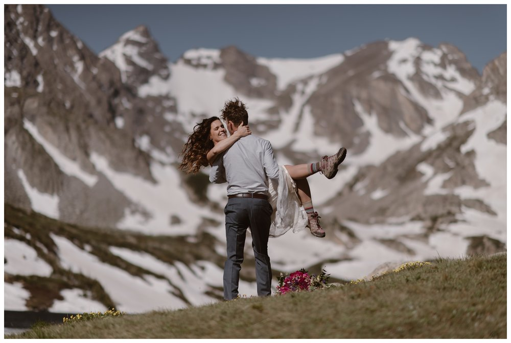 The snowy peaks of Nederland, Colorado look like the Swiss Alps as Karen and Matt embrace following their high alpine lake elopement ceremony at Lake Isabelle. Photo by Adventure Instead, Maddie Mae.