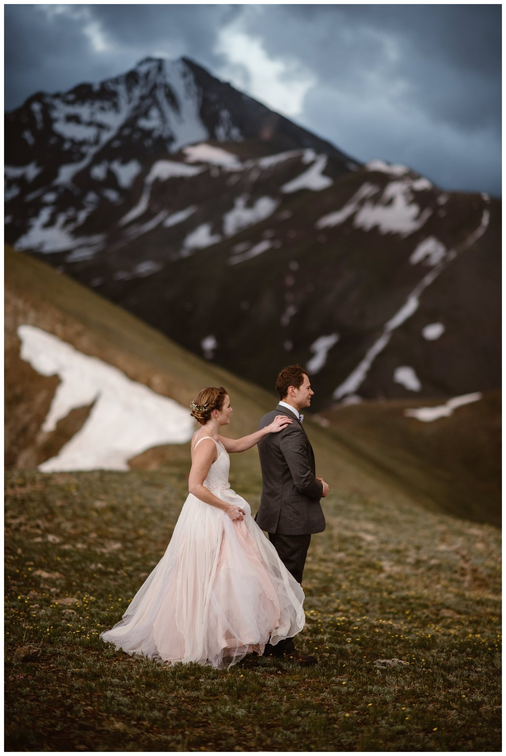 Marcela taps Vasily on the shoulder for their first look with the jagged peaks of the Sawatch Range of the Rocky Mountains behind them before their intimate two person elopement. Photo by Maddie Mae, Adventure Instead.