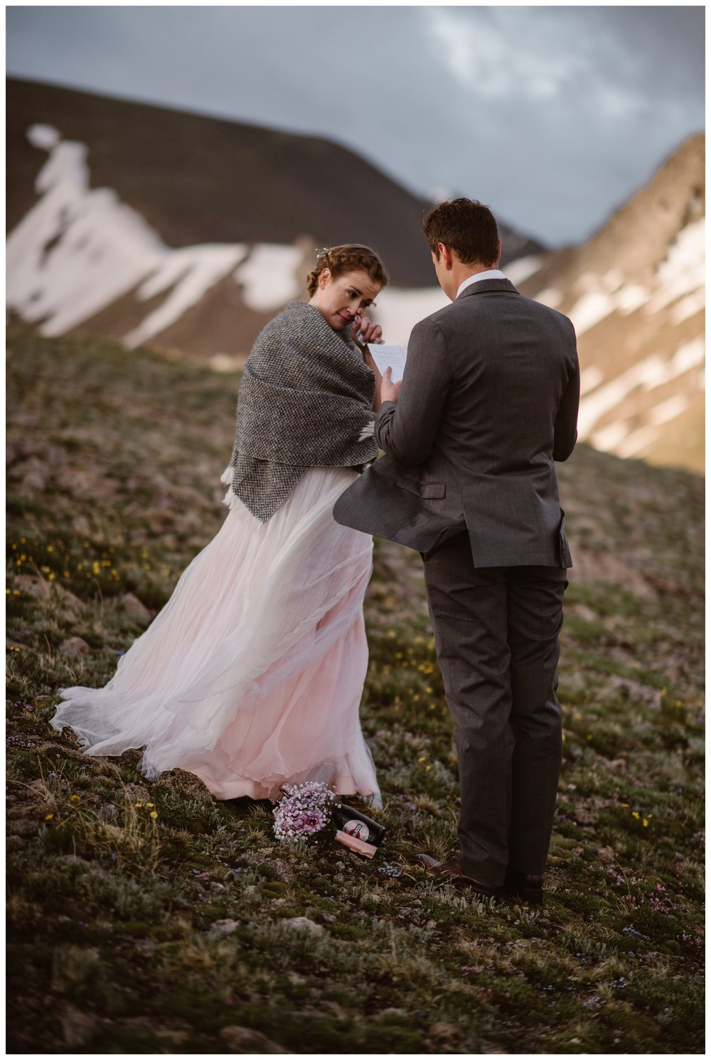 Wrapped in a blanket as alpine winds whip around her, Marcela wipes away a tear while Vasily reads his vows during their intimate two person self solemnizing elopement ceremony on the top of Independence Pass. Photo by Maddie Mae, Adventure Instead.