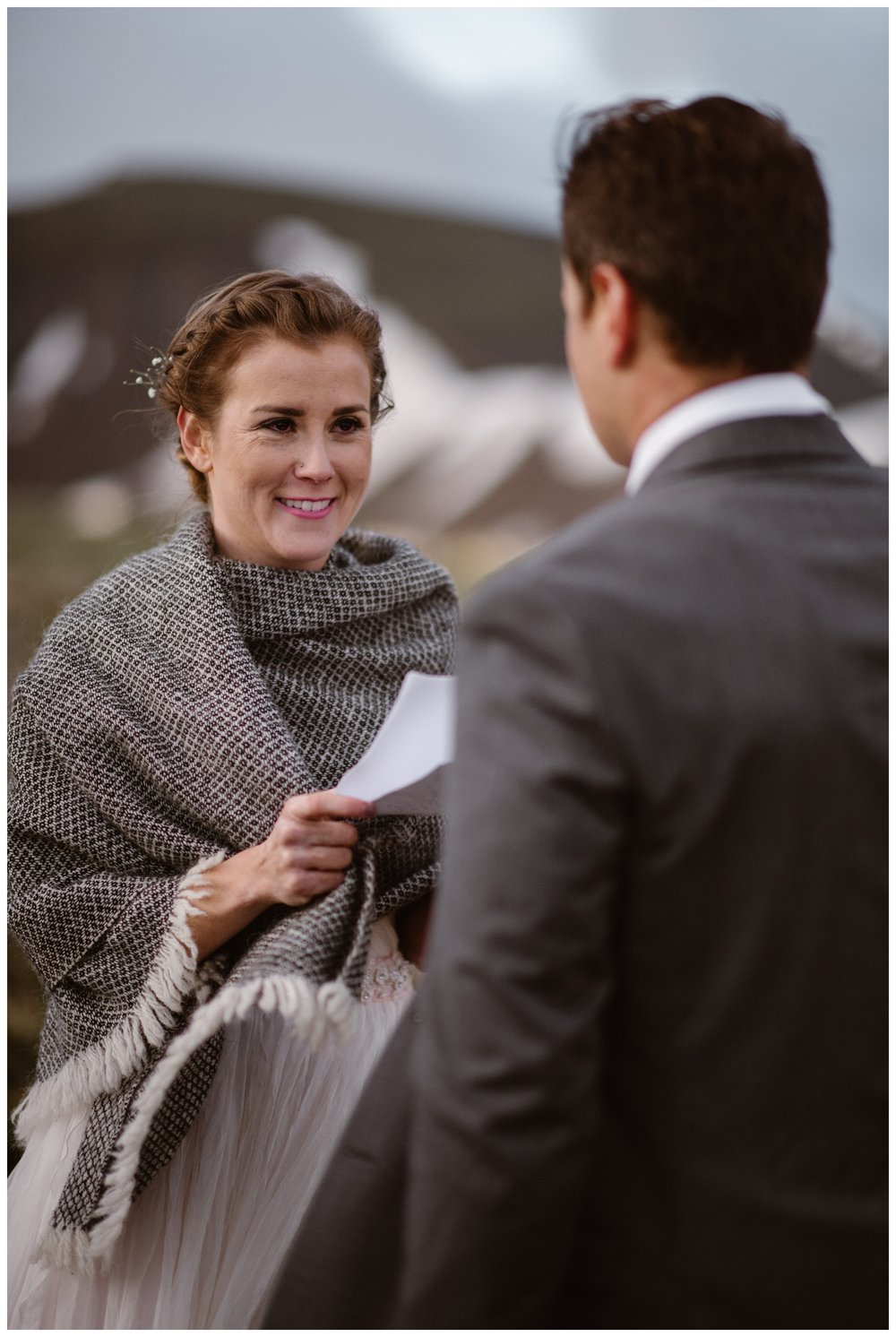 Her blush wedding dress covered in a blanket to protect her from high winds at the top of Independence Pass, Marcela reads her vows during their intimate two person elopement ceremony. Photo by Maddie Mae, Adventure Instead.