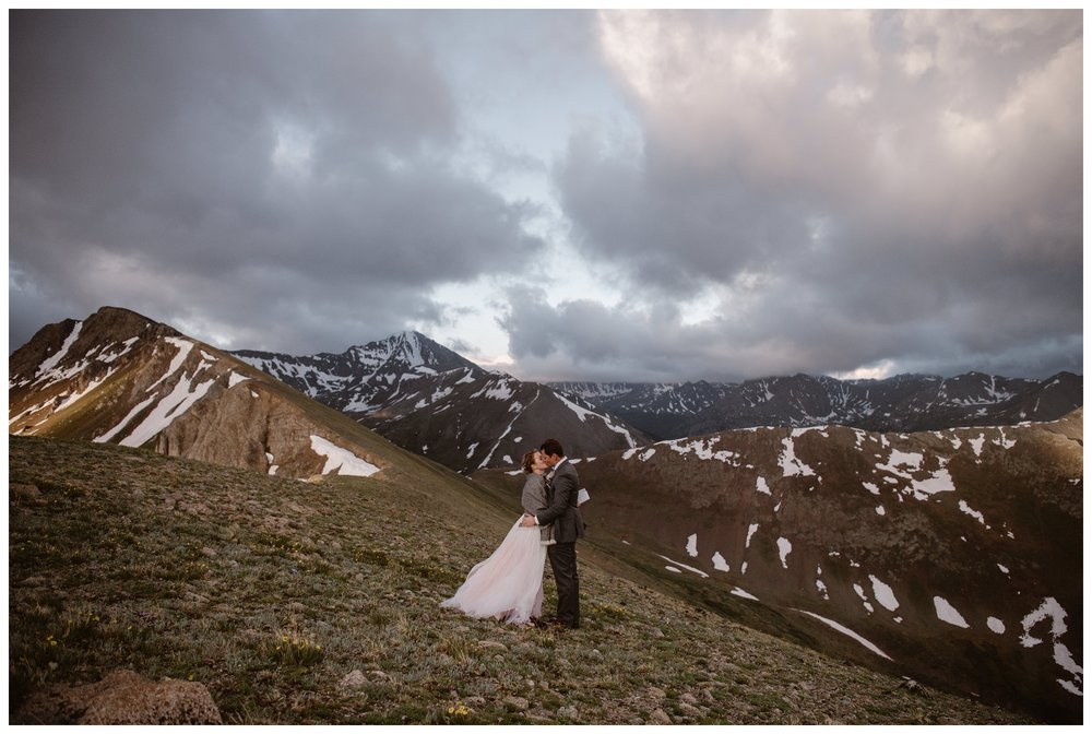 With the jagged mountains of the Sawatch Range glowing pink around them, Marcela and Vasily share their first kiss after their intimate self solemnizing elopement ceremony. Photo by Maddie Mae, Adventure Instead.