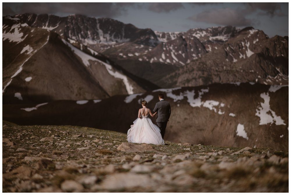 Stunningly jagged peaks lit by the rising sun loom before Marcela and Vasily as they walk away from their hiking elopement ceremony on the top of Independence Pass. Photo by Maddie Mae, Adventure Instead.