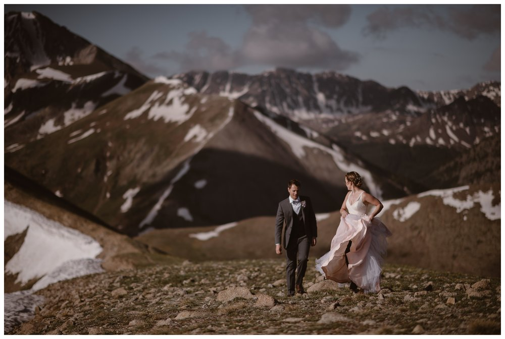 Marcela's blush wedding dress was layered with both blush and white layers. It blew beautifully in the wind on the Continental Divide above Independence Pass. Photo by Maddie Mae, Adventure Instead.