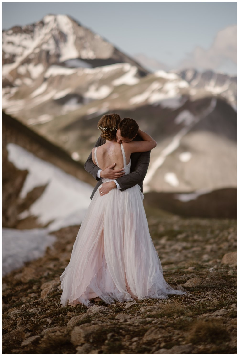 Newlyweds Marcela and Vasily share an emabrace on the top of Independence Pass following their intimate self solemnizing elopement. Photo by Maddie Mae, Adventure Instead.