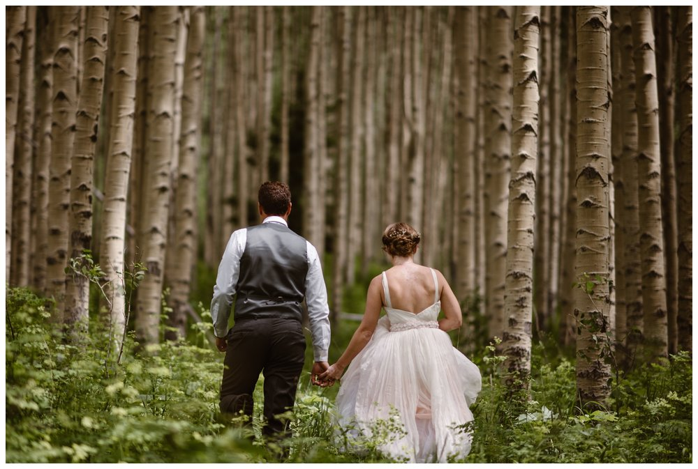 Following their elopement ceremony at the top of Independence Pass, Marcela and Vasily hike through old growth aspen forests outside the Maroon Bells. Photo by Maddie Mae, Adventure Instead.