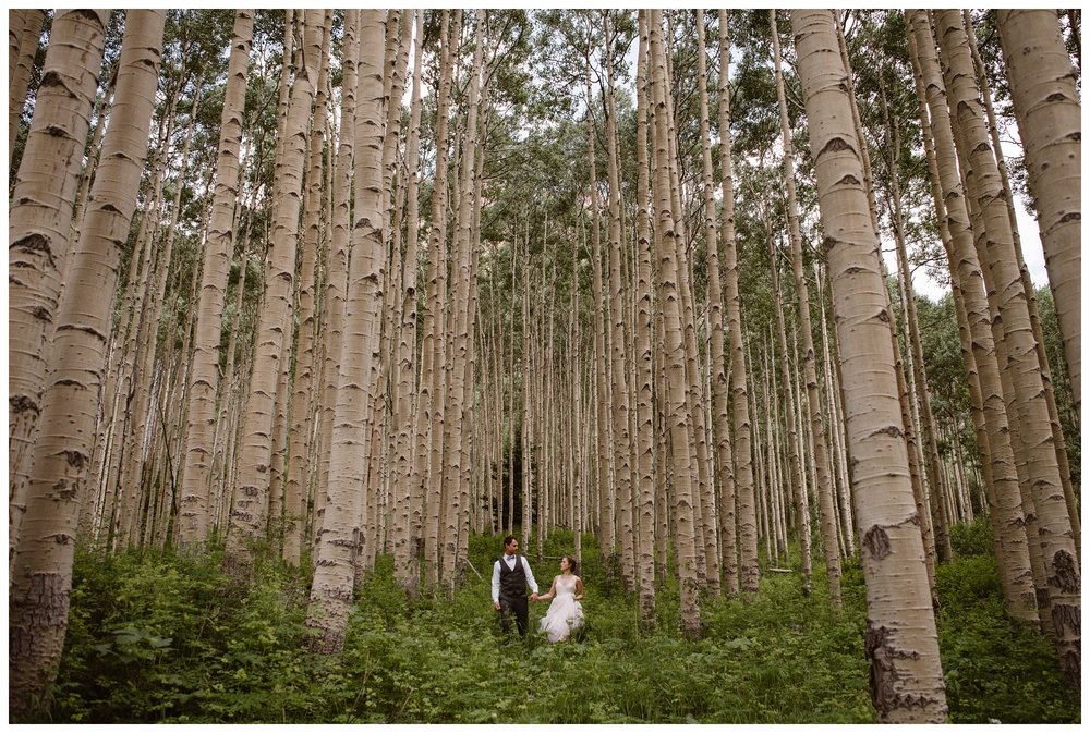 Old growth aspen forest towers above Marcela and Vasily outside the Maroon Bells following their outdoor self solemnizing elopement ceremony. Photo by Maddie Mae, Adventure Instead.