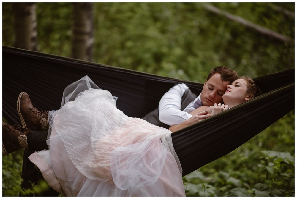 Marcela and Vasily embrace outside in a pack hammock while surrounded by giant aspen trees in a forest outside the Maroon Bells in Aspen, Colorado. Photo by Maddie Mae, Adventure Instead.