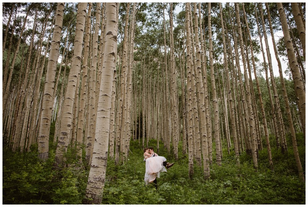 Surrounded by giant old aspen trees, Marcela and Vasily embrace following their intimate self solemnizing elopement ceremony. Photo by Maddie Mae, Adventure Instead.