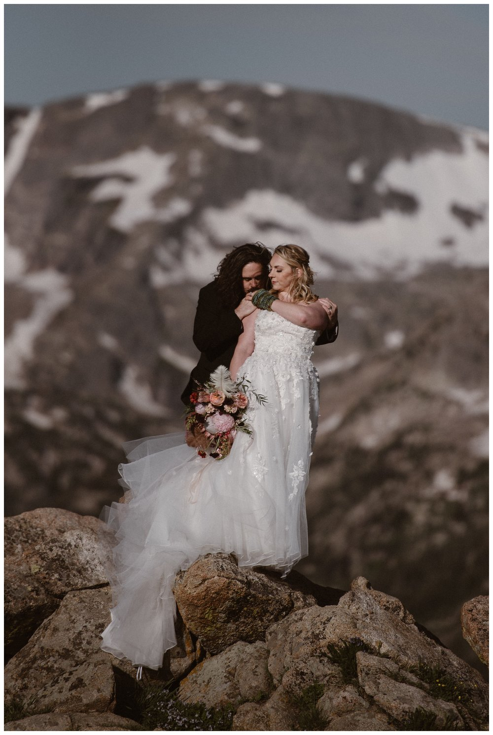 With the snow capped Rocky Mountains behind them, Alicia and Zach embrace at the top of Trail Ridge Road for their first look ahead of their elopement ceremony. Photo by Adventure Instead, Maddie Mae.