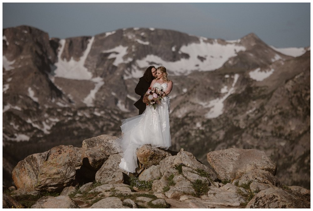 The snow capped Rockies behind them, Alicia and Zach embrace standing on top of the rocks at Trail Ridge Road in Rocky Mountain National Park for their first look before their elopement ceremony. Photo by Adventure Instead, Maddie Mae.