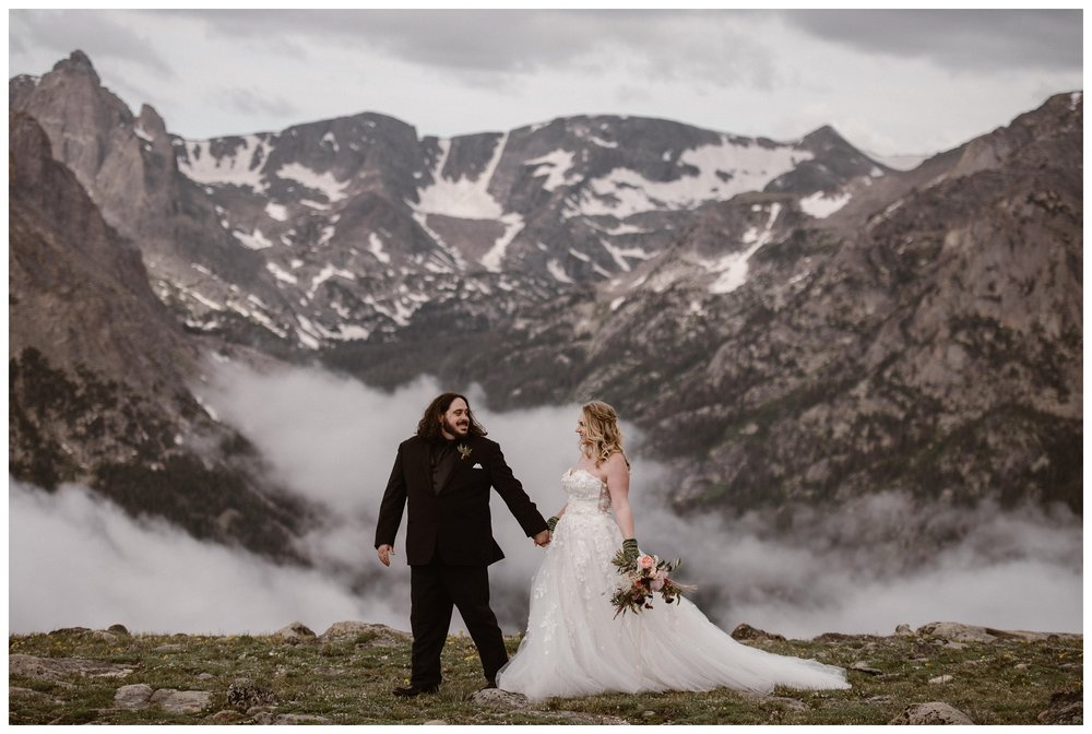 Alicia and Zach walk through the top of Trail Ridge Road for their adventurous couple's portraits in Rocky Mountain National Park before their intimate elopement. Photo by Adventure Instead, Maddie Mae.