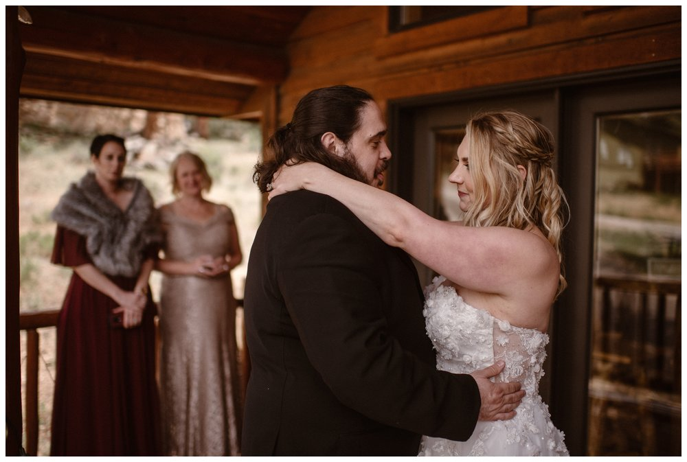 Alicia and Zach share their first dance as a married couple surrounded by family and friends at a cabin in Estes Park after their Rocky Mountain National Park elopement. Photo by Adventure Instead, Maddie Mae.