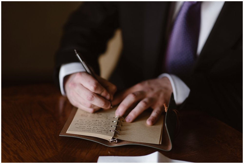 Austin, the groom, writes his vows by hand before his snowy wintery elopement ceremony. Photo by Adventure Instead, Maddie Mae Elopement Photographers.