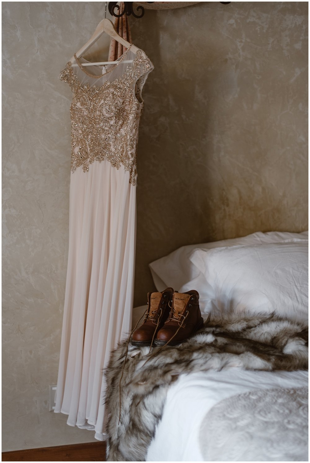 Marlayna's wedding gown hangs in Georgetown, Colorado while her boots and fur lay on the bed before her winter elopement ceremony. Photo by Adventure Instead, Maddie Mae Elopement Photographers.