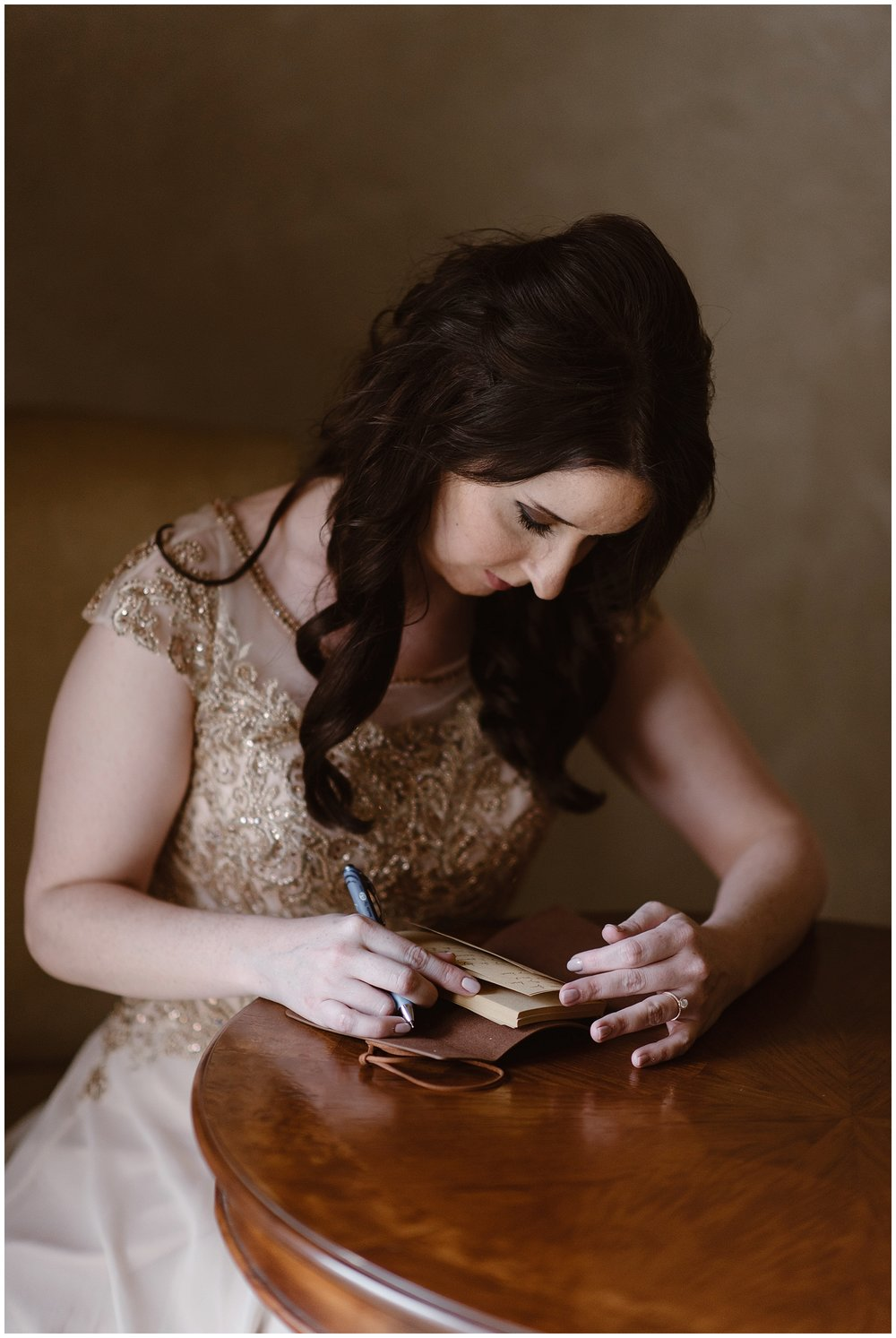 Marlayna writes out her wedding vows by hand before her elopement ceremony at the snowy Sapphire Point in Dillon, Colorado. Photo by Adventure Instead, Maddie Mae Elopement Photographers.