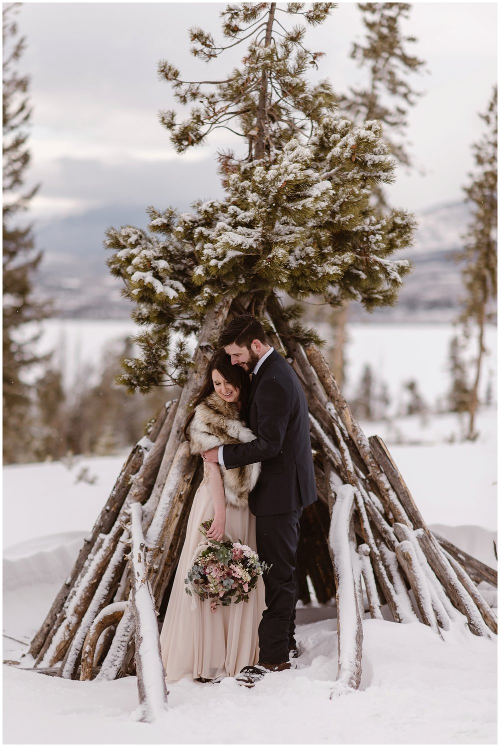 Marlayna and Austin embrace in a wooden snow structure outside Breckenridge, Colorado following their snowy winter elopement ceremony. Photo by Adventure Instead, Maddie Mae Elopement Photographers.