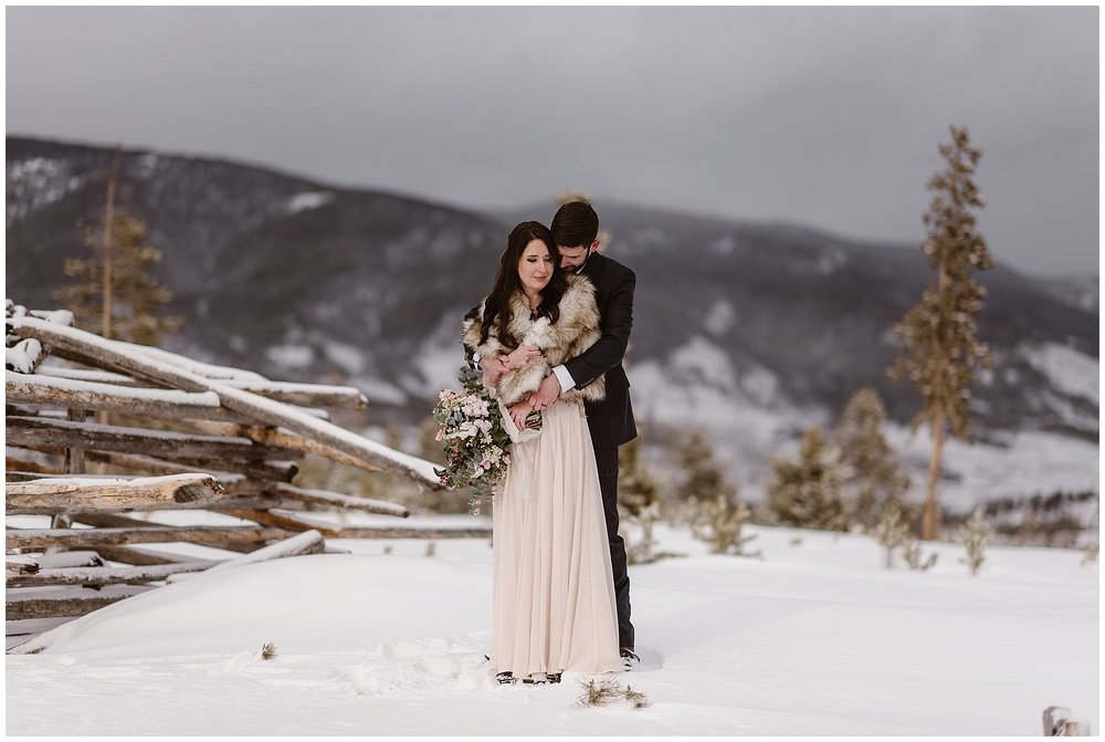 The snow capped Rockies behind them, Marlayna and Austin embrace following their winter elopement ceremony at Sapphire Point in Dillon, Colorado. Photo by Adventure Instead, Maddie Mae Elopement Photographers.