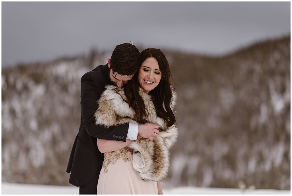 A few tips to stay warm during your winter elopement ceremony: wear underlayers, invest in a coat or fur, and take lots of breaks throughout the day to warm up. Photo by Adventure Instead, Maddie Mae Elopement Photographers.