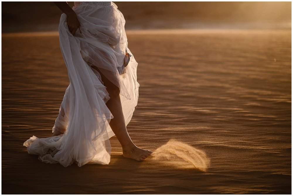 Bride kicks up sand in the Namibian desert at sunset after her elopement. Eloping at sunrise or sunset gives you dramatic photos and an incredible experience on your elopement wedding day. Where you elope and how you say your vows matters! Photo by Maddie Mae, Adventure Instead Elopement Photographers.