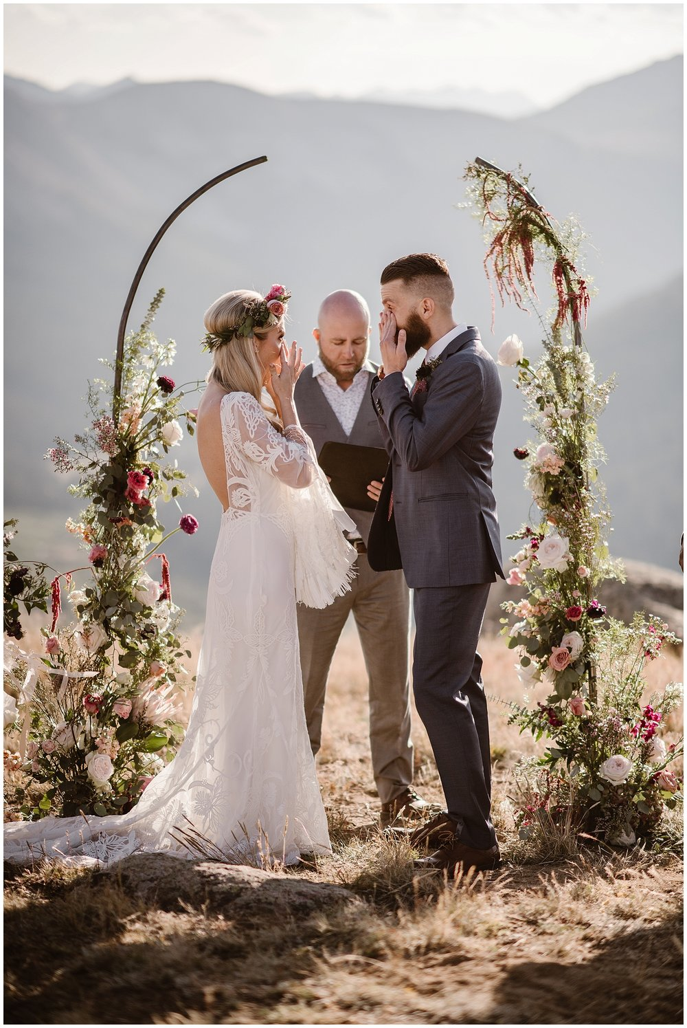 This couple chose to elope with an officiant and a backdrop of a stunning arch with flowers. Where you elope and how you say your vows matters! Photo by Maddie Mae, Adventure Instead Elopement Photographers.