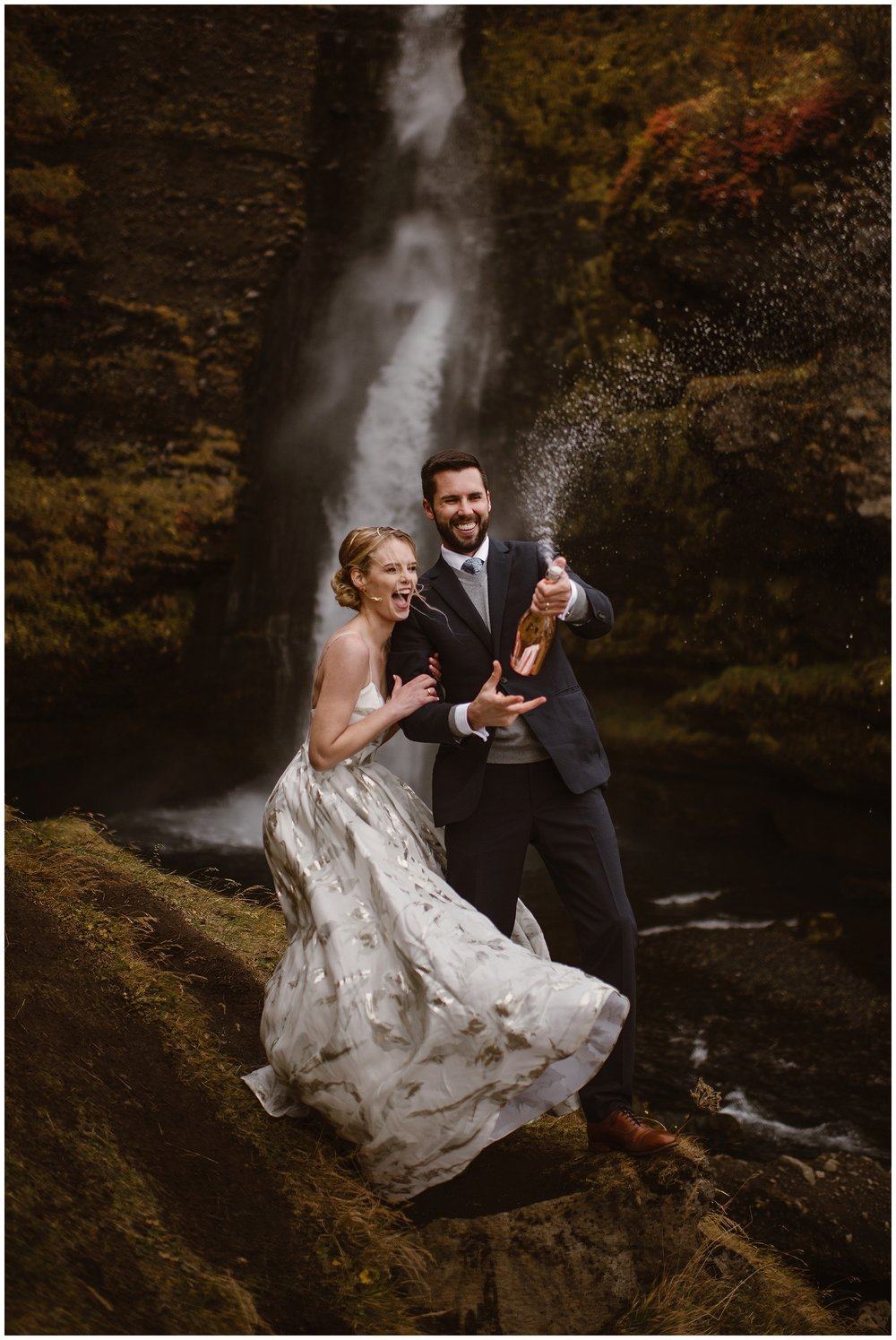Celebrate your dream destination elopement by spraying a bottle of champagne, like this couple who eloped near a waterfall in Iceland. Photo by Maddie Mae, Adventure Instead Elopement Photographers.