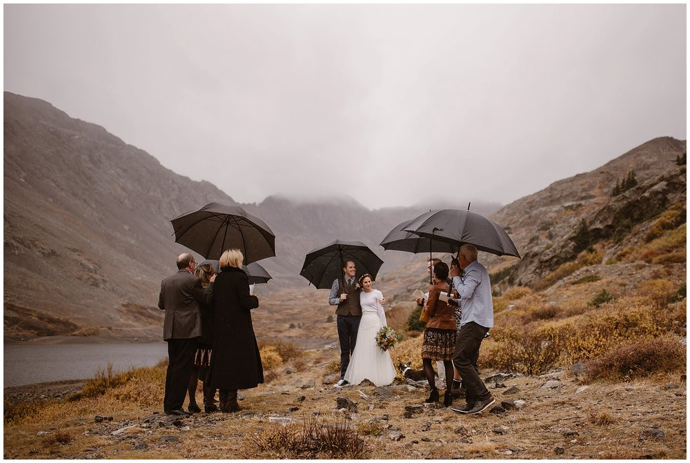 Even a little rain shouldn't stop the adventure of your elopement day. You can also have guests, including family and friends, at your ceremony and still call it an elopement! Where you elope and how you say your vows matters! Photo by Maddie Mae, Adventure Instead Elopement Photographers.