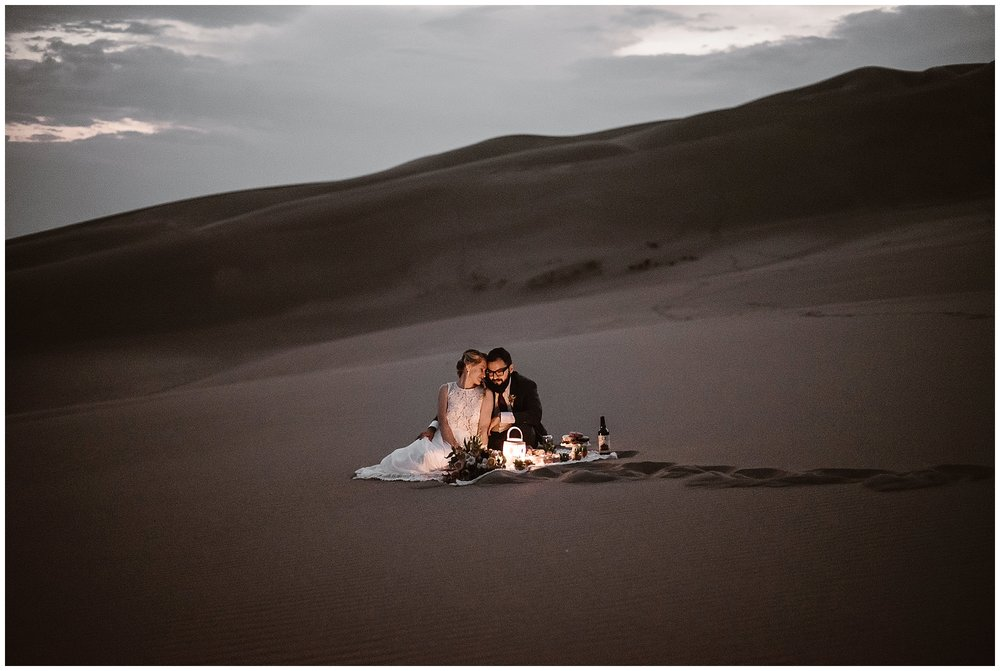 Traditional elements of a wedding day can still happen during an elopement. Plan a special time to eat and drink with your partner after saying your vows, like this couple who had a picnic by lantern light as the sunset on the Great Sand Dunes National Park. Where you elope and how you say your vows matters! Photo by Maddie Mae, Adventure Instead Elopement Photographers.