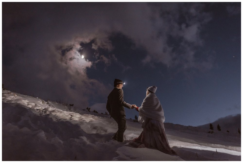 You can elope in winter! This couple planned a mountain hiking elopement ceremony and walked through frozen snow fields at night after saying their vows. Where you elope and how you say your vows matters! Photo by Maddie Mae, Adventure Instead Elopement Photographers.