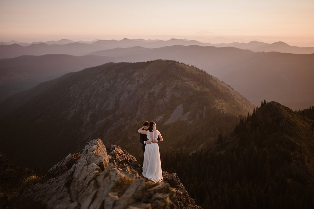 A couple embraces on a mountain peak in the midst of a golden alpenglow as they exchange their vows. Moody Pacific Northwest elopement photo taken by adventure elopement photographer Adventure Instead.